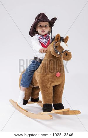 Little Children Consepts. Assured Little Caucasian Girl in Cowgirl Clothing Posing On Symbolic Horse Against White Background. Vertical Image Composition