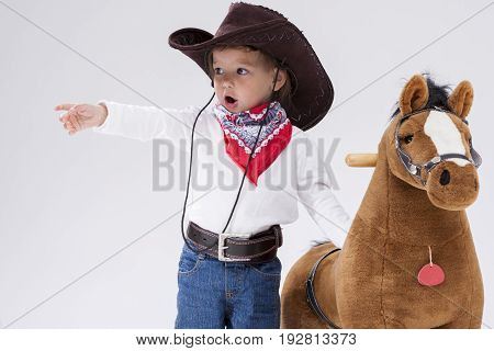 Little Children Consepts. Caucasian Girl in Cowgirl Clothing Posing With Symbolic Plush Horse Against White. Directing Forward. Horizontal Image Orientation