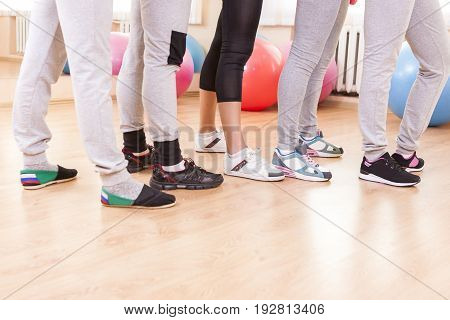 Closeup of Feet of Five Female Athletes Posing Together in Sport Venue.Horizontal Image Composition