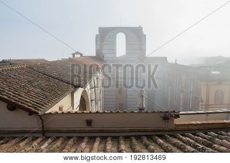 Italy Siena - December 26 2016: the view of the tiled roofs and incomplete facade of the planned Duomo nuovo in fog. Facciatone on December 26 2016 in Siena Tuscany Italy.