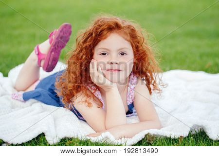 Portrait of cute adorable pensive little red-haired Caucasian girl child in blue dress lying on green grass in park outside dreaming thinking happy lifestyle childhood concept