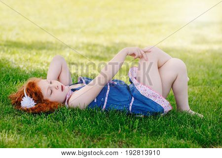 Portrait of cute adorable little red-haired Caucasian girl child in blue dress lying on grass in park outside looking up in sky happy lifestyle childhood concept