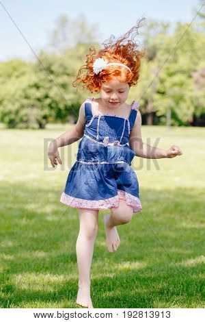 Portrait of cute adorable little red-haired Caucasian girl child in blue dress jumping on grass in meadow park outside funny candid moment happy lifestyle childhood concept