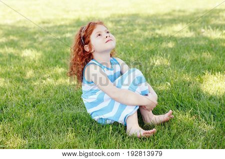 Portrait of cute adorable little red-haired Caucasian girl child in blue dress sitting in field meadow park outside looking up in the air having fun happy lifestyle childhood concept