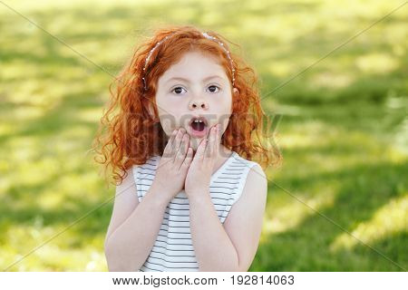 Portrait of cute adorable surprised little red-haired Caucasian girl child in striped dress in park outside playing crying screaming in fear happy lifestyle childhood concept