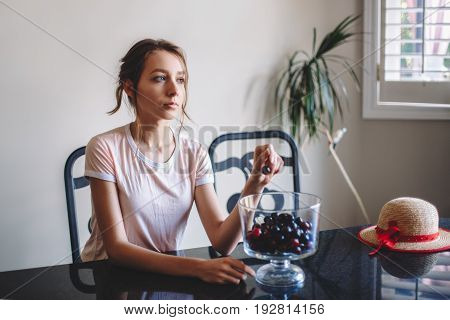 Portrait of young beautiful white Caucasian woman girl sitting at table eating cherries summer day indoors at home toned with retro filters film effect candid lifestyle