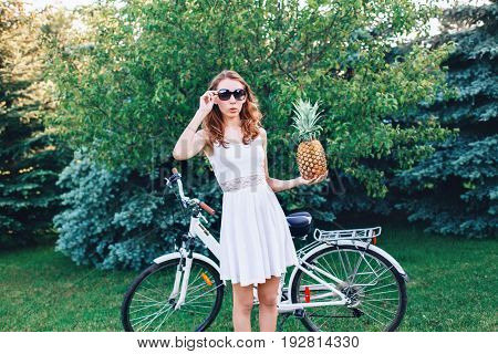 Portrait of young beautiful white Caucasian woman girl in sunglasses holding pineapple fruit standing with bike in park outside on summer day modern contemporary fashion