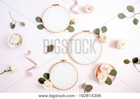 Embroidery frames with beige rose flower buds and eucalyptus on pale pastel pink background. Flat lay top view decorated concept.