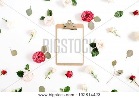 Flat lay floral frame with clipboard red and beige rose flower buds pattern on white background. Top view decorated concept.