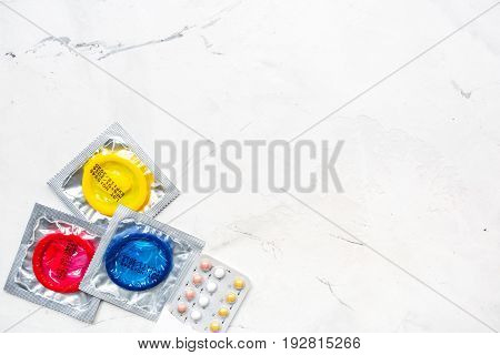 safe sex with condom contraception on white desk background top view