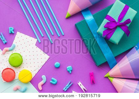 Birthday wrapped gifts and party hats on purple background top view.
