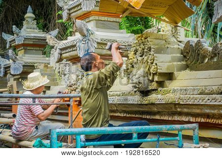 BALI, INDONESIA - APRIL 05, 2017: Unidentified couple using a chisel to do art of cement, in Ubud Bali located in Indonesia.