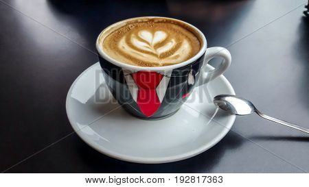 Coffee cup with an original red tie picture on a black background
