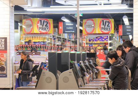 MELBOURNE AUSTRALIA - JUNE 14, 2017: Unidentified people use self check out cashers at Coles supermarket.