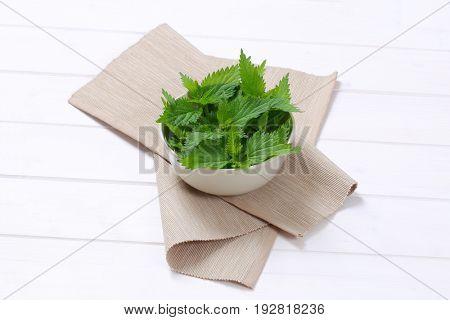 bowl of fresh nettle leaves on beige place mat