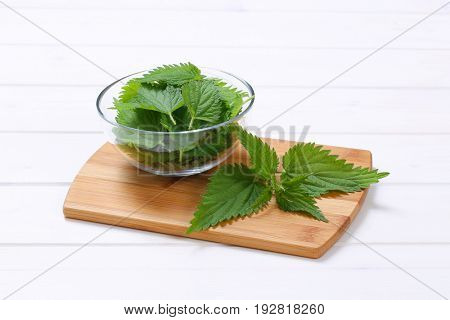 bowl of fresh nettle leaves on wooden cutting board