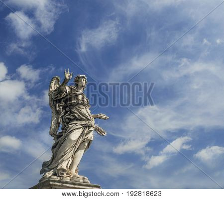 Angel statue holding the Nails of Holy Cross with heavenly sky on Sant'Angelo Bridge in the center of Rome