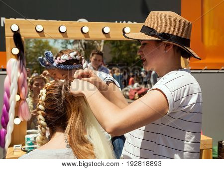 Khabarovsk Russia - May 27 2017: Fashion hair stylist plaiting braids with fake extensions on a customer. Young Caucasian women in front of a mirror at a hair salon