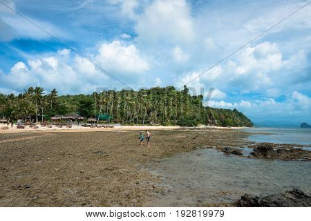 EL NIDO, PALAWAN, PHILIPPINES - MARCH 29, 2017: Couple walking on the rocks to get the sand at Las Cabanas Beach