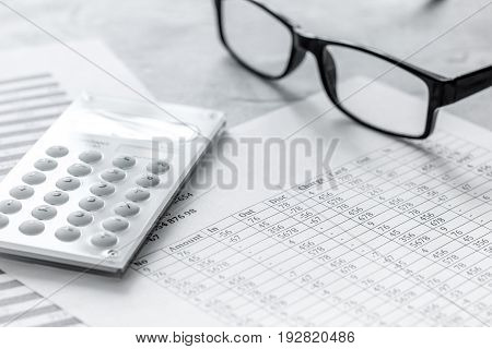 Business report preparing with calculator and glasses on office desk background