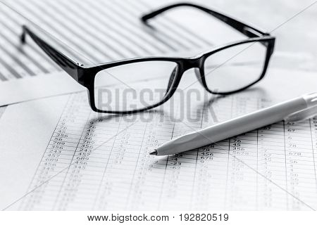 Business report preparing with pen and glasses on office desk background