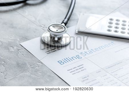 stethoscope, billing statement for doctor's work in medical center on stone background