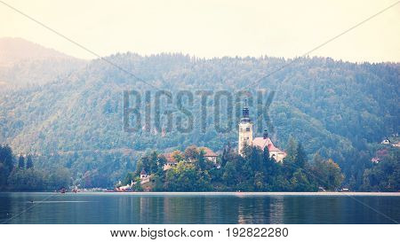 Old church on small island in the middle of lake with gondolas flowing on watter, Bled Lake Slovenia