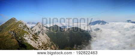 High mountain ridge hidden in clouds during sunrise, Koschuta, Slovenia