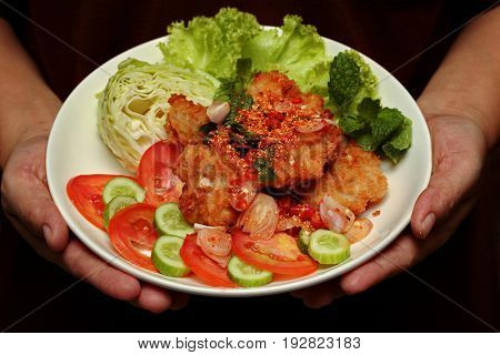 Thai food Spicy crispy deep-fried chicken salad call Yum Kai Zap in Thai topped cucumber green oakcabbage and tomato.