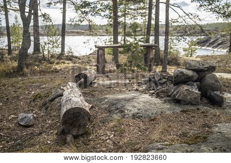 Camp on the rocky shore of the lake. An old wooden table a bench of logs and a place for a fire among the pines.