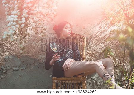 wine glass in hand of woman or fashion model sitting on chair in sunny yard on outdoor wall. Alcohol drinking. Enjoying life. Holiday celebration. Spring or summer bloom