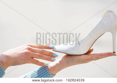 shoe. footwear white color leather on female hand on blurred background fashion and beauty shopping and presentation cinderella copy space poster