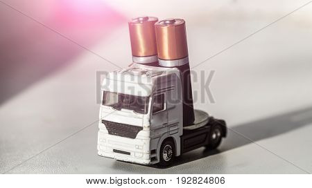 toy truck or car carrying two AA batteries power supply elements on white background. Transportation delivery and shipment. Energy electricity charge technology and accumulator