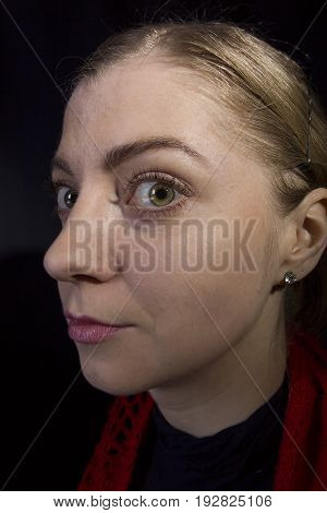 Strange young blonde woman close-up on a black background