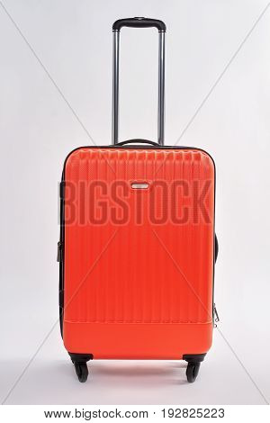 Red suitcase with metal handle. Large closed case, white background.
