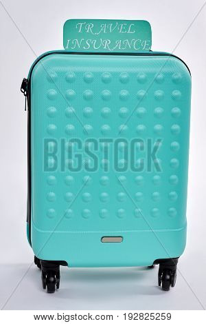 Wheeled blue suitcase, paper note. Travel with insurance. Be in safety abroad.