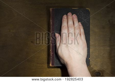 Female hand on the Bible on an old wooden background