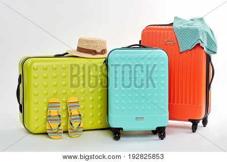Three different suitcases, summer clothes. Accessories for voyage trip.