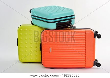 Suitcases on wheel, white background. Colorful objects for voyage trip.