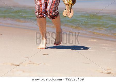 Woman Walking Holding Flip Flops