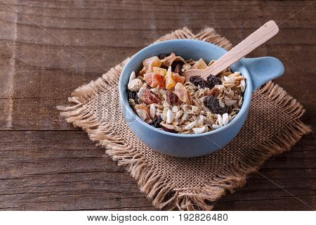 Bowl of healthy gluten free muesli with nuts seeds and dried berries over rustic wooden background. Clean eating Healthy living Vegan Vegetarian Gluten free food concept