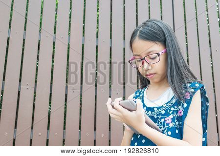 Beautiful Girl Using Tablet To Learning In The Park. Concept Technology Education.