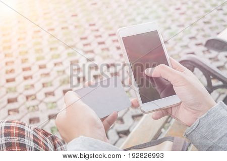 Selective Focus Woman's Hand Using Smartphone With Blank Credit Card For Business In The Park. Conce