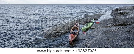 Two kayaks parked on the rocky shore of the lake spring evening. Panorama.