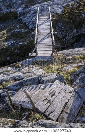 Small old wooden bridge and stairs on a rocky island spring day.