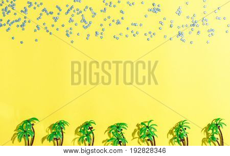 Palm trees and stars flat lay on yellow background