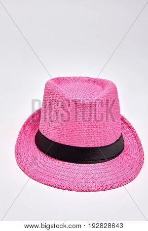 Pink woven hat, white background. Summer headgear accessory for beach.