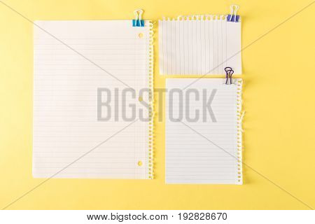 Blank sheets of paper on a yellow background