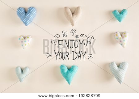 Enjoy Your Day message with blue heart cushions on a white paper background