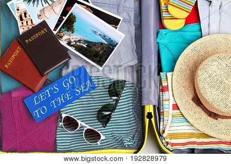 Traveler suitcase ready for trip. Full luggage of summer accessories.
